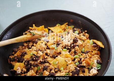 Vegan tofu scramble chilaquiles with beans, scallions and lime - Stock Photo