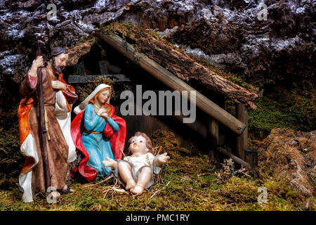 Close-up of the Christmas Nativity scene. Hut with baby Jesus in the manger, with Mary and Joseph - Stock Photo