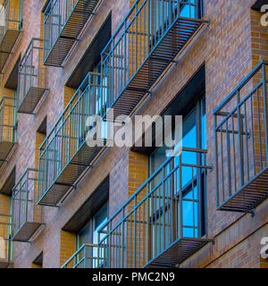 Narrow and airy balconies of a brick building. Close up view of a building's tiny and open balconies with metal railings and floor. The building has r - Stock Photo