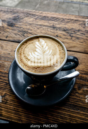 Hot Delicious Cappuccino Coffee served on blue cup on wooden table... - Stock Photo