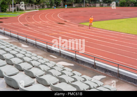 Selective focus on seats in a stadium with a man running in the background - Stock Photo