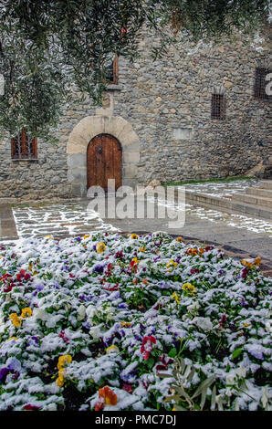 Beautiful street of Andorra la Vella city caught by sudden snow. Blooming colorful live flowers under snow cover at foreground. General Council of And - Stock Photo