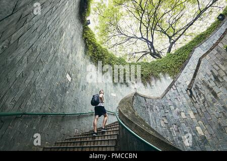 Young man (tourist) walking up on the spiral staircase of underground walkway in Singapore. - Stock Photo