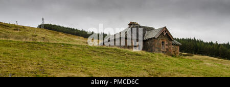 A stone cottage stands partially derelict on bleak open moorland in Strath Bran in the Highlands of Scotland. - Stock Photo
