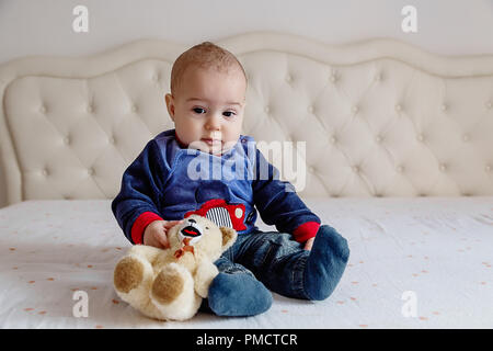 Baby boy in a blue sweater and orange hair sitting on a white bed with a soft toy bear. - Stock Photo