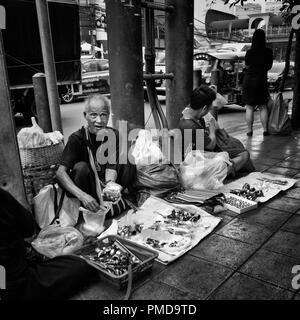 an old seller of objects in a street in the center of Bangkok, Thailand - Stock Photo