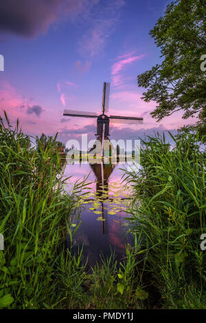 Old dutch windmill and a canal at sunset in Kinderdijk, Netherlands. This system of 19 windmills was built around 1740 and is a UNESCO heritage site. - Stock Photo