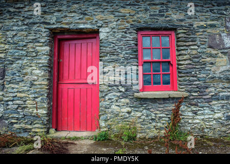 A vintage door and window on a facade of an old cottage built of stones in Ireland - Stock Photo
