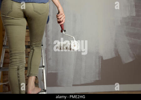 Home improvement. Beautiful woman painting wall with paint roller. - Stock Photo