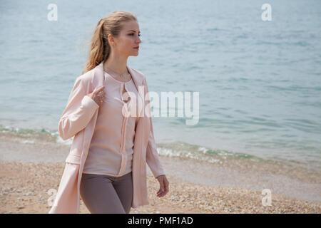 blonde girl in autumn walks on the Beach Ocean - Stock Photo
