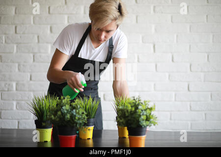 Young Asian boy takes care of indoor plants - Stock Photo