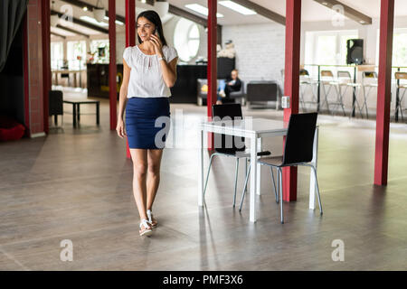 Beautiful Woman Talking On Phone Walking In Office. Portrait Of Stylish Smiling Business Woman In Fashionable Clothes Calling On Mobile Phone In Office - Stock Photo