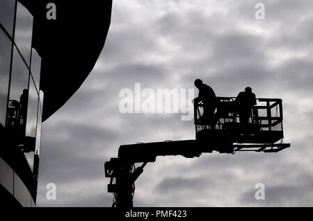 Two construction workers in silhouette against grey sky on a hydraulic lifting ramp - Stock Photo