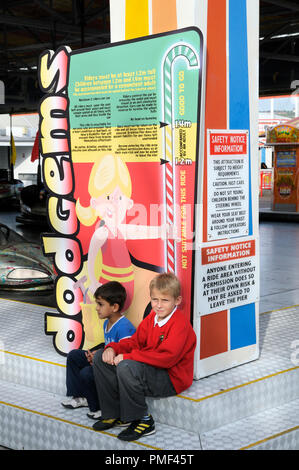 Two young boys sitting under a height restrictions board for a dodgems ride at the funfair - Stock Photo