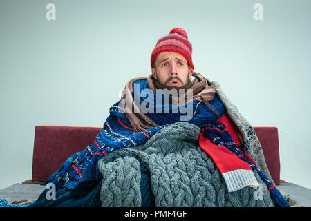 Bearded sick man with flue sitting on sofa at home or studio covered with knitted warm clothes. Illness, influenza concept. Relaxation at Home. Healthcare Concepts. - Stock Photo