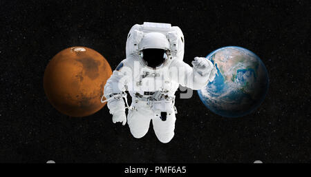 Astronaut is traveling to a new home on the planet Mars. Spaceman in the open space against the backdrop of the planet Earth and Mars. The concept of  - Stock Photo