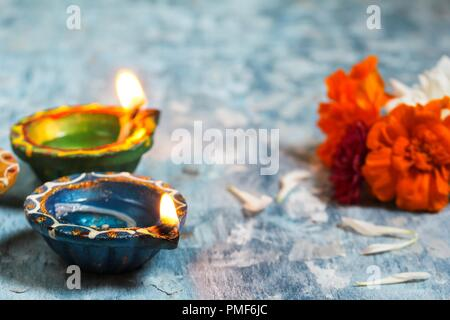 Happy Diwali - Colorful Clay Diya lit during Deepavali festival of lights, selective focus - Stock Photo