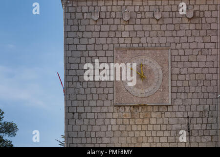 Tower made of stone tiles with clock. Clock are in a square, inner circle, roman numbers. Big square, historic part of town Krk, island Krk, Croatia. - Stock Photo