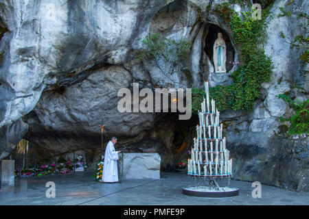 Lourdes (south-western France): grotto of Massabielle, Our Lady of Lourdes sanctuary. Faithful praying in front of the grotto (not available for postc - Stock Photo