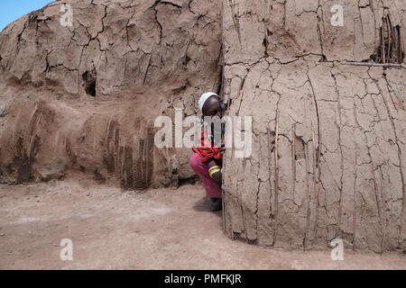 Maasai woman sits at the entrance to a traditional hut made from branches pasted with fresh cow-dung and mud which bakes hard under the hot sun in the Ngorongoro Conservation Area in the Crater Highlands area of Tanzania Eastern Africa - Stock Photo