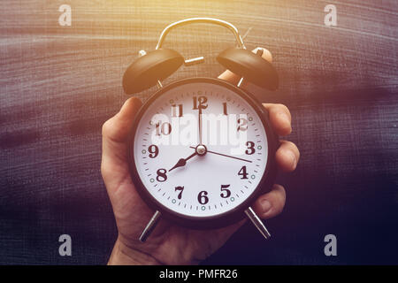Eight o'clock in the morning, time for school. Teacher holding classic alarm clock over dirty chalkboard surface. - Stock Photo