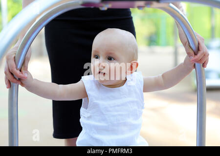 Cute Ten Month Old Baby Boy Playing At Outdoor Playground. Close Up View - Stock Photo