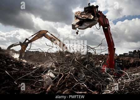 Like Dinosauria, the excavators work with special grippers through huge tents made of steel wires, which were collected during the construction work on the grounds of the former Phoenixstahlwerk in Dortmund Hoerde. Where in 2003 Chinese workers dismantled a complete steel and rolling mill at record speed and rebuilt it in China. - Stock Photo