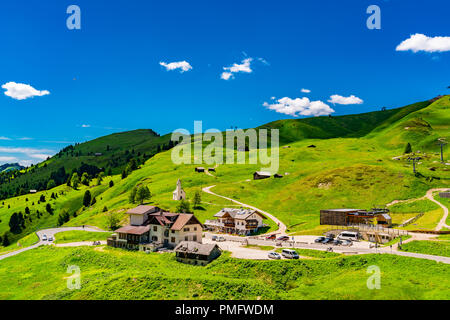 View of the mountain at the Gardena Pass in South Tyrol Italy with the village and the small church on the hill - Stock Photo