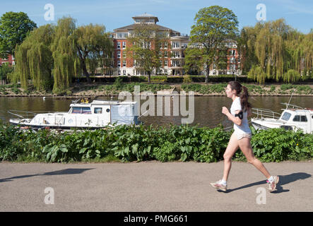 young female jogger beside the river thames at richmond, surrey, england, with apartments blocks of east twickenham in distance - Stock Photo