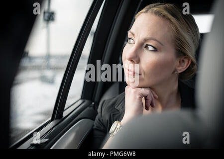 Thoughtful businesswoman travelling in car - Stock Photo