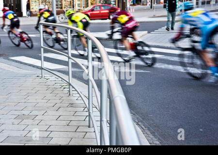 professional cyclists sprinting during a city road bicycle racing - Stock Photo