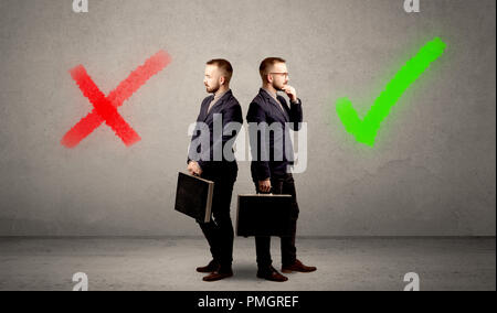 Young conflicted businessman choosing between a right and a wrong direction - Stock Photo