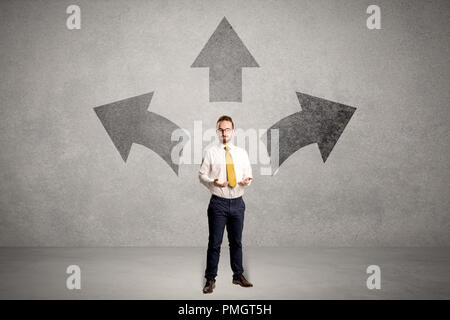 Charming businessman in doubt, choosing from three directions in front of a grey wall  - Stock Photo