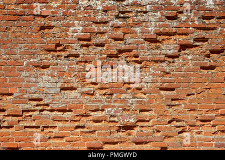 Very old weathered, damaged, badly repaired red brick wall close up full frame background - Stock Photo