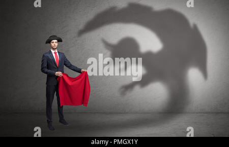 Businessman standing with red cloth in his hand and imp shadow on the background  - Stock Photo