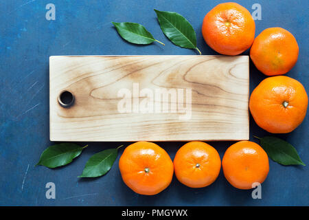 An empty cutting board and tangerines on a blue background. Place for text, top view - Stock Photo