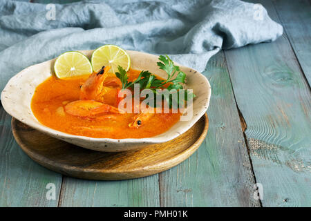 Soup with shrimps on a wooden rustic green table. Selective focus. - Stock Photo