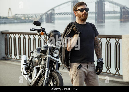Redhead bearded biker holding leather jacket on shoulder and standing near motorbike on bridge - Stock Photo