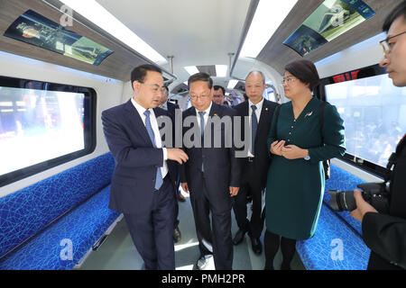 18 September 2018, Berlin: A Chinese delegation walks through a Chinese subway train of the company CRRC at the railway fair Innotrans. The train will be presented in a world premiere on the exhibition grounds between the halls under the radio tower. A Saxon company was involved in the development of the train. Photo: Wolfgang Kumm/dpa - Stock Photo
