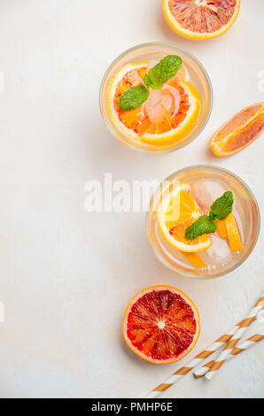 Cold refreshing drink with blood orange slices in a glass on a white concrete background. Top view, flat lay, copy space. - Stock Photo