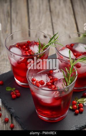 Refreshing drink with cranberries and rosemary on wooden  background. - Stock Photo