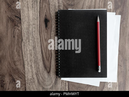 black spiral notebook and pen on wooden table - Stock Photo