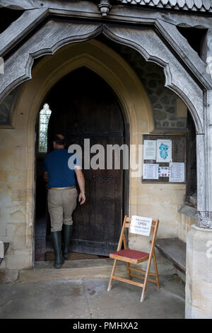 A visitor enters St. Michael and All Angels church where a sign asks people to close the door after them, on 10th September 2018, in Lingen, Herefordshire, England UK. - Stock Photo