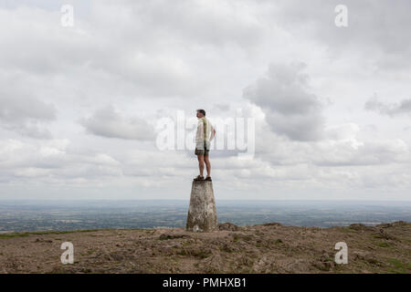 A hill climber stands on the top of the trig-point and looks across distant landscapes from the top of The Beacon, on 15th September 2018, in Malvern, Worcestershire, England UK. Worcestershire Beacon, also popularly known as Worcester Beacon, or locally simply as The Beacon, is a hill whose summit at 425 metres (1,394 ft)[1] is the highest point of the range of Malvern Hills that runs about 13 kilometres (8.1 mi) north-south along the Herefordshire-Worcestershire border, although Worcestershire Beacon itself lies entirely within Worcestershire. A triangulation station, also known as a triangu - Stock Photo