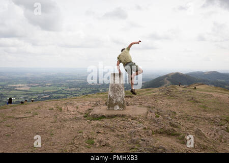 A hill climber jumps down off the trig-point on the top of The Beacon, on 15th September 2018, in Malvern, Worcestershire, England UK. Worcestershire Beacon, also popularly known as Worcester Beacon, or locally simply as The Beacon, is a hill whose summit at 425 metres (1,394 ft)[1] is the highest point of the range of Malvern Hills that runs about 13 kilometres (8.1 mi) north-south along the Herefordshire-Worcestershire border, although Worcestershire Beacon itself lies entirely within Worcestershire. A triangulation station, also known as a triangulation pillar, trigonometrical station, trig - Stock Photo