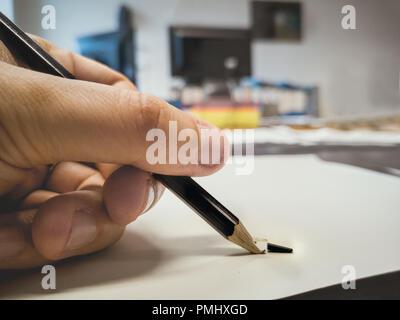 broken pencil hand office background left-handed - Stock Photo