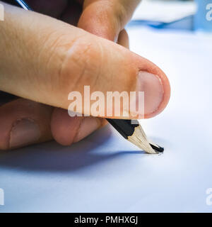 broken pencil hand blue background square format - Stock Photo