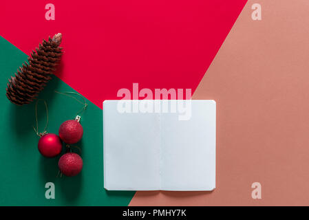 Christmas concept in a minimal style with a white empty notebook, red Christmas balls, and a pine cone, on a red, green and orange background. - Stock Photo