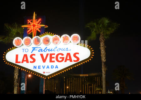 The Welcome To Las Vegas Sign At Night With Palm Trees In The Background