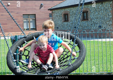 Two small boys on a circular swing in a play park - Stock Photo